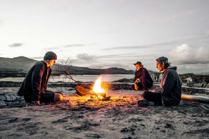 Three young adult males sitting near a fire by the beach in the pacific northwest