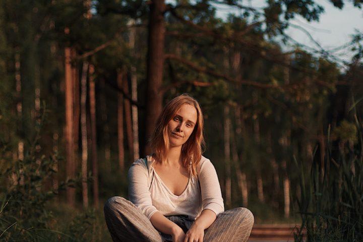 woman sitting cross-legged outside