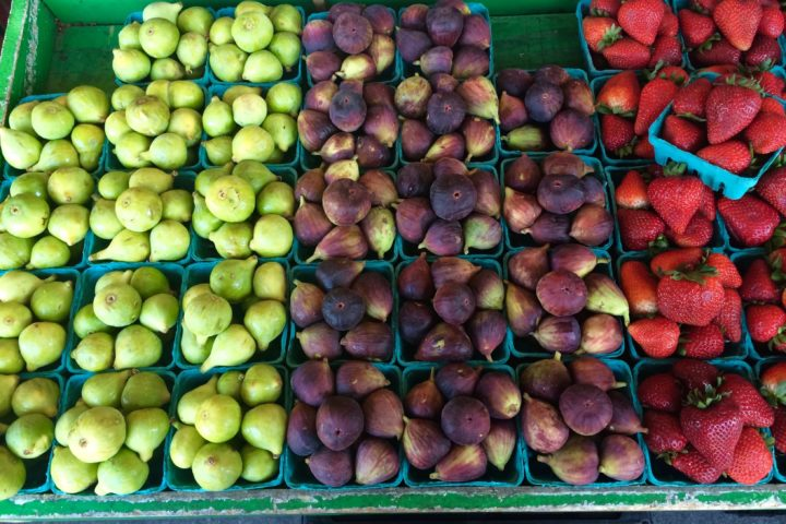 multiple cartons of different fruits at a market