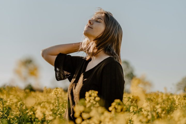 peaceful woman smiling in a field of flowers