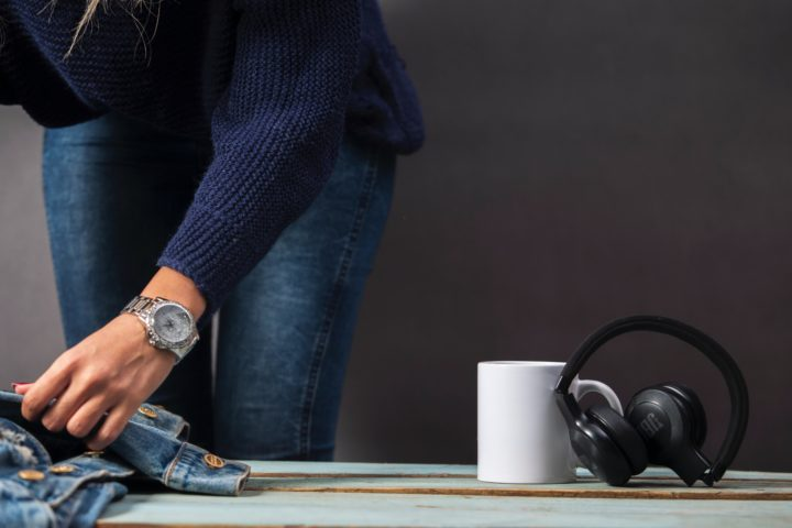 hearing protection next to a coffee mug while a woman gets ready for the day