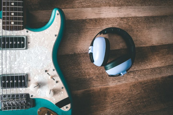 ear protective ear muffs next to a guitar