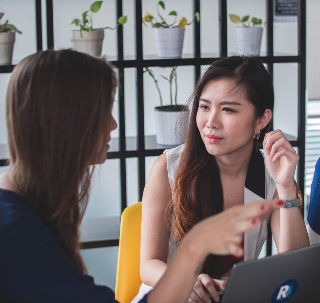 Two women talking in fron of open laptop